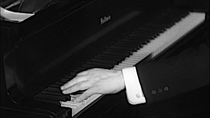 A pianist's left hand on the piano. Black and White.