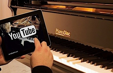 Piano keyboard with a tablet showing the YouTube logo